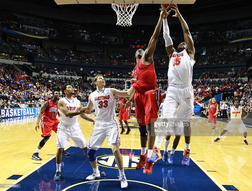 Reginald Buckner #23 of the Ole Miss Rebels goes up between Will Yeguete #15 and Erik Murphy #33 of the Florida Gators in the second half of the SEC Basketball Tournament Championship game at Bridgestone Arena on March 17, 2013 in Nashville, Tennessee.