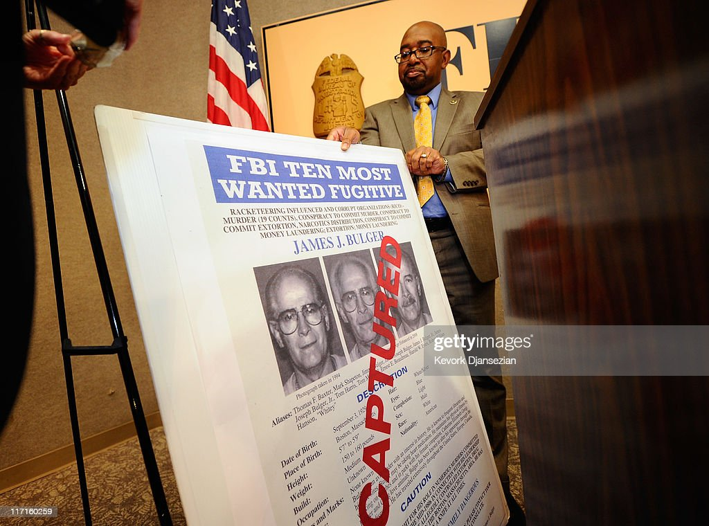 Reginald Chapple FBI Community Outreach Specialist adjusts a poster featuring fugitive Boston crime boss James 'Whitey' Bulger during a news...