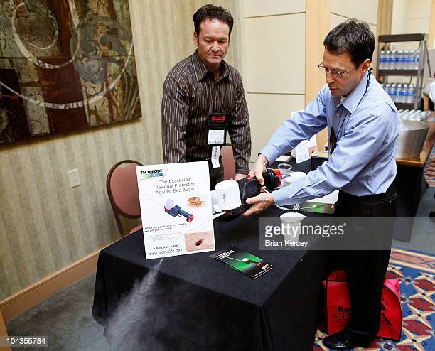 Reginald Coler tries out a powdered insecticide applicator as he talks with the product's representative Jim Harper at the Bed Bug University North...