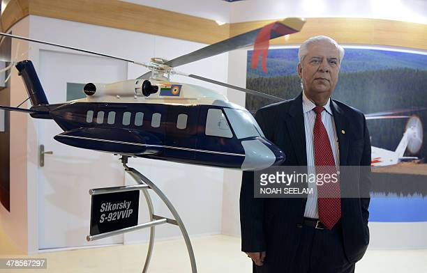 Regional Executive India and South Asia of Sikorsky AJS Walia poses beside a model of Sikorsky S92 helicopter on display in an exhibitors venue at...