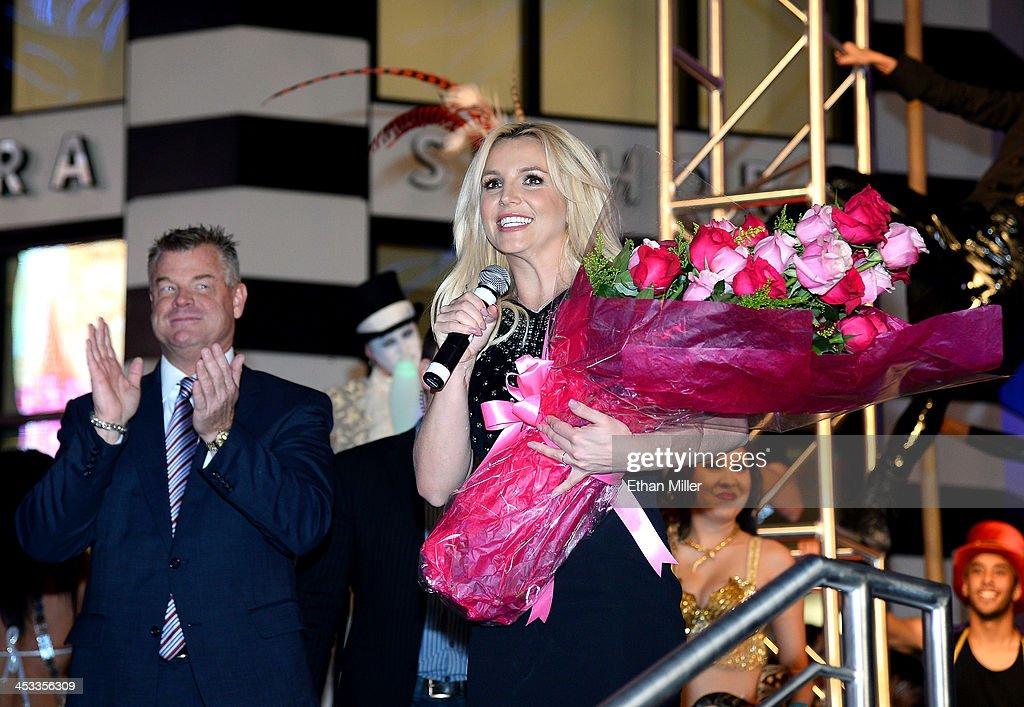 Regional President of Planet Hollywood Resort & Casino, Bally's Las Vegas and Paris Las Vegas David Hoenemeyer (L) looks on as singer Britney Spears holds a bouquet of flowers at a welcome ceremony as she celebrates the release of her new album 'Britney Jean' and prepares for her two-year residency at Planet Hollywood on December 3, 2013 in Las Vegas, Nevada. Spears' show 'Britney: Piece of Me' will debut at the resort on December 27, 2013.