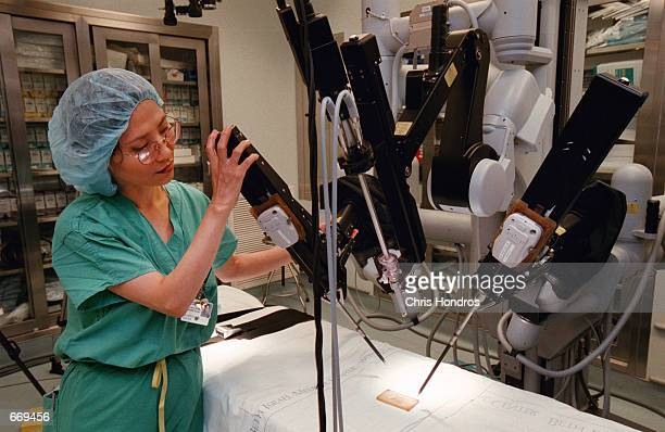 Registered nurse Haesook Lee adjusts a surgical robot July 20 2000 at Beth Israel Medical Center in New York City The robot one of three of its kind...