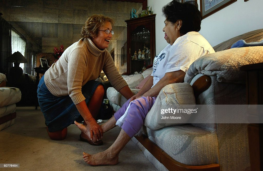 Registered nurse Susan Eager (L) checks the feet of Jane Awise, who suffers from severe diabetes, while performing a home visit on November 4, 2009 in Denver, Colorado. Awise has health insurance but says she pays about $400 each month in co-pays to treat her chronic disease. Eager works for the Dominican Sisters Home Health Agency, a non-profit that performs some 25,000 home visits each year in the Denver area. It provides free home nursing care to patients with chronic diseases, helps them to better manage their disabling illnesses and provides custodial services with the aim of keeping patients in their homes and out of more expensive nursing home care.