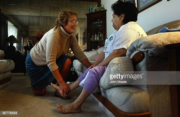Registered nurse Susan Eager checks the feet of Jane Awise who suffers from severe diabetes while performing a home visit on November 4 2009 in...