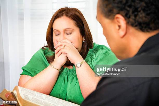 Regretful woman prays eyes closed while clergyman reads her Bible