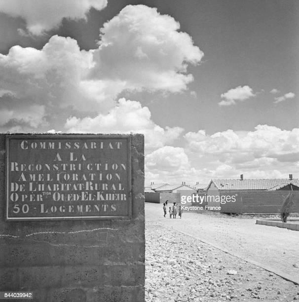 Regroupement de populations civiles en Oranie panneau d'entrée sur lequel est écrit 'Amélioration de l'habitat rural' à Oued El Kheir Algérie en 1961