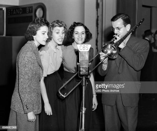 Rehearsal for CBS Radio program Chesterfield Time featuring big band orchestra leader and trombonist Glenn Miller far left with the Andrews Sisters...