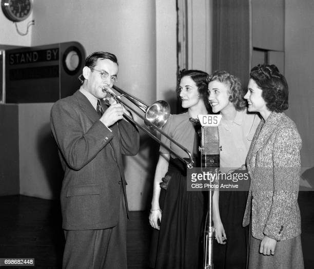 Rehearsal for CBS Radio program Chesterfield Time featuring big band orchestra leader and trombonist Glenn Miller far right with the Andrews Sisters...