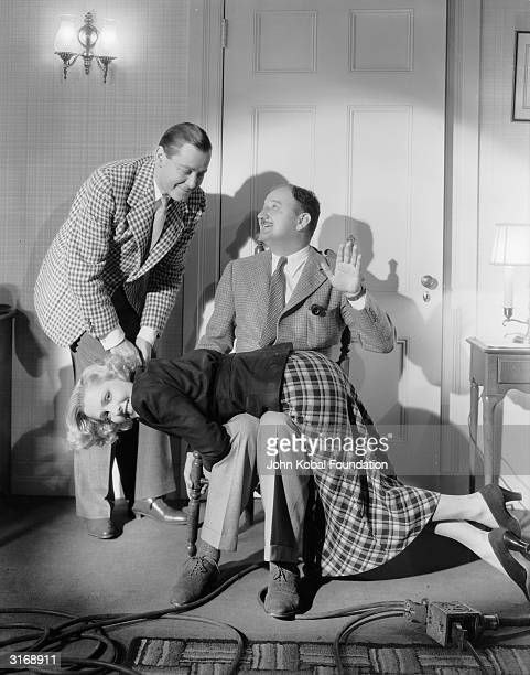 Rehearsing a scene an amused Jean Arthur gets a spanking watched by Herbert Marshall during the filming of 'If You Could Only Cook' directed by...