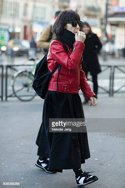 Rei Kawakubo Comme des Garcons creative director enters the Gosha Rubchinskiy show in a red Comme des Garcons leather jacket black sunglasses a black...
