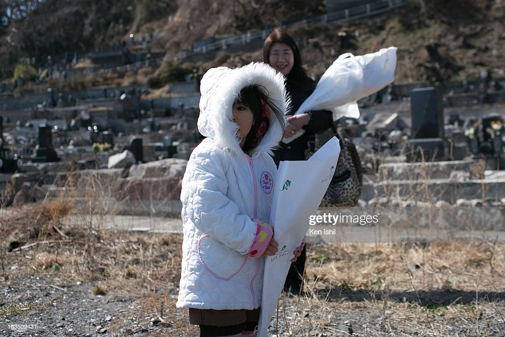 Rei Tanaka, 3, holds a bouquet of flowers as she attends a memorial service for her grandparents and other victims of the tsunami at Kouganji Temple on March 11, 2013 in Otsuchi, Iwate, Japan. On March 11 Japan commemorates the second anniversary of the magnitude 9.0 earthquake and tsunami that claimed more than 18,000 lives.