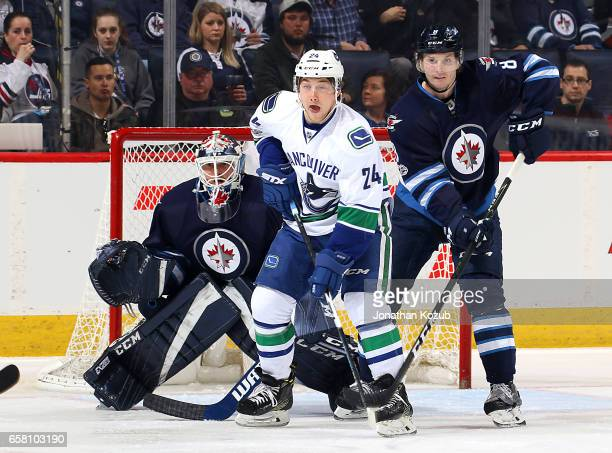 Reid Boucher of the Vancouver Canucks goaltender Michael Hutchinson and Jacob Trouba of the Winnipeg Jets keep an eye on the play during first period...