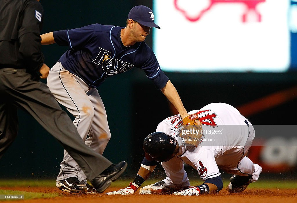 Reid Brignac #15 of the Tampa Bay Rays attempts to tag out Carlos Santana #41 of the Cleveland Indians during the game on May 11, 2011 at Progressive Field in Cleveland, Ohio.