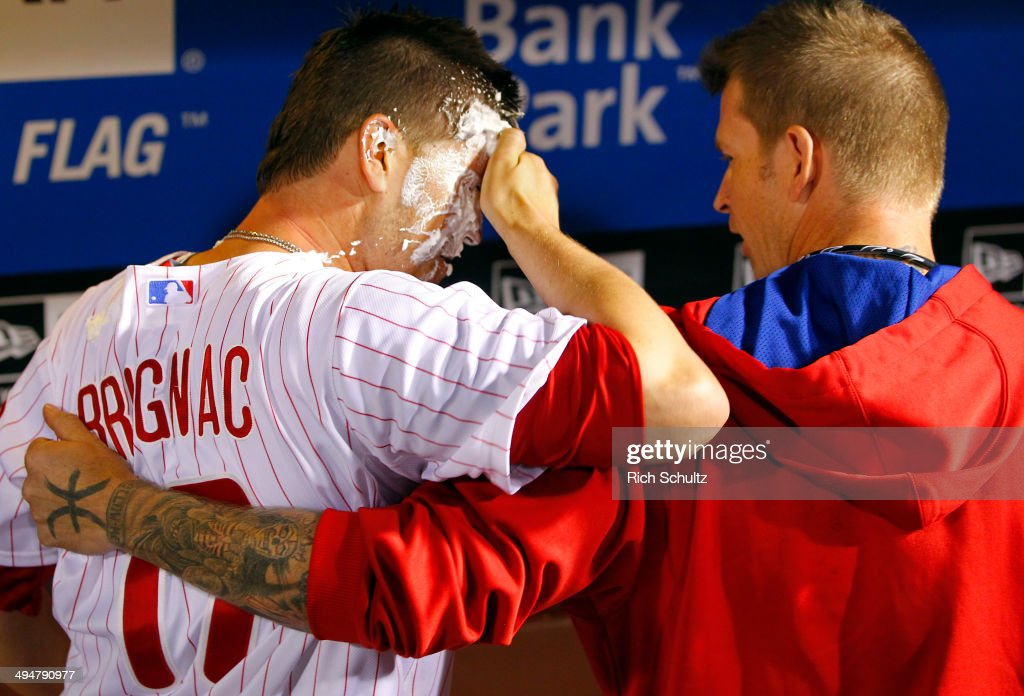 <a gi-track='captionPersonalityLinkClicked' href=/galleries/search?phrase=Reid+Brignac&family=editorial&specificpeople=4175431 ng-click='$event.stopPropagation()'>Reid Brignac</a> #17of the Philadelphia Phillies is hugged by teammate <a gi-track='captionPersonalityLinkClicked' href=/galleries/search?phrase=A.J.+Burnett&family=editorial&specificpeople=213103 ng-click='$event.stopPropagation()'>A.J. Burnett</a> #34 who hit him with a towel full of shaving cream after Brignac hit the game winning single in the fourteenth inning to defeat the New York Mets 6-5 during a game at Citizens Bank Park on May 30, 2014 in Philadelphia, Pennsylvania.