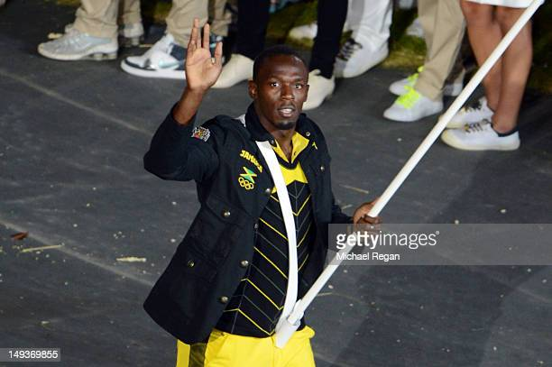 Reigning Olympic Men's 100m and 200m champion Usain Bolt of the Jamaica Olympic athletics team carries his country's flag during the Opening Ceremony...