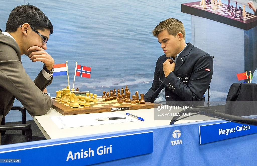 Reigning world champion <a gi-track='captionPersonalityLinkClicked' href=/galleries/search?phrase=Magnus+Carlsen&family=editorial&specificpeople=2602660 ng-click='$event.stopPropagation()'>Magnus Carlsen</a> (R) makes a move during his match against Russian-born Dutch chess prodigy Anish Giri at the first matchday of the 77th Tata Steel Chess Tournament in Wij aan Zee, on January 9, 2015. The tournament will take place from 9 till 25 January in its traditional location of Wijk aan Zee, but will also visit Rotterdam and The Hague.