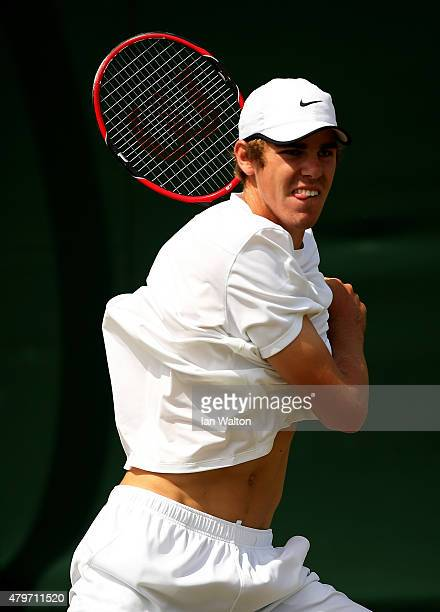 Reilly Opelka of the United States returns a shot in his Boy's Singles First Round match against Alex De Minaur of Australia during day seven of the...