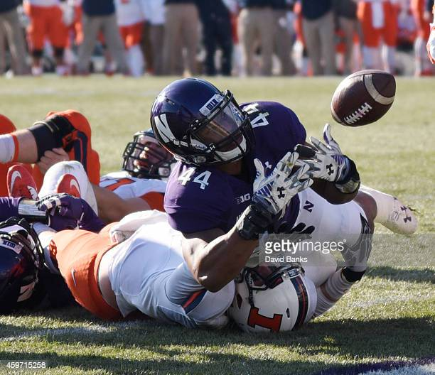Reilly O'Toole of the Illinois Fighting Illini loses control of the ball as he is tackled by Chi Chi Ariguzo of the Northwestern Wildcats during the...
