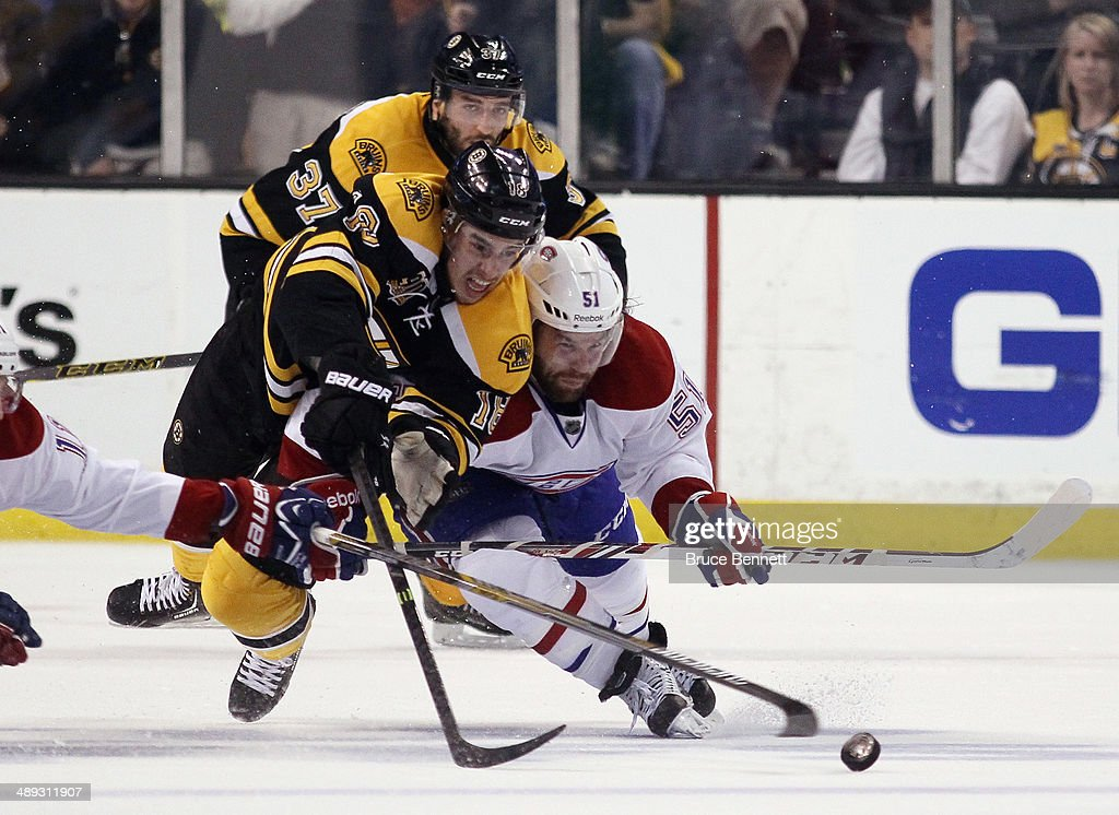 Reilly Smith of the Boston Bruins and David Desharnais of the Montreal Canadiens battle for the puck during the second period during Game Five of the...