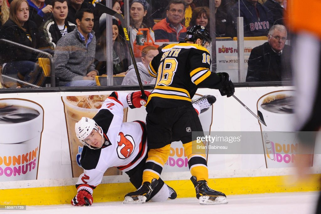 Reilly Smith #18 of the Boston Bruins checks against Marek Zidlicky #2 of the New Jersey Devils at the TD Garden on October 26, 2013 in Boston, Massachusetts.