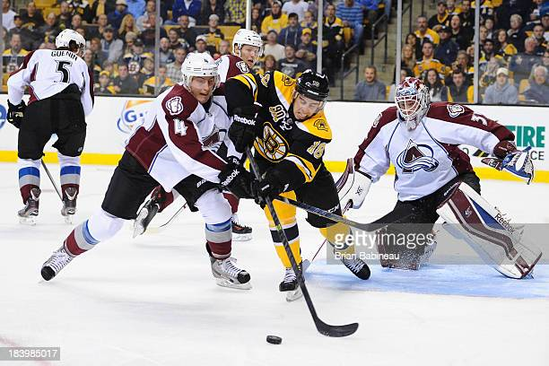 Reilly Smith of the Boston Bruins fights for the puck against Tyson Barrie of the Colorado Avalanche at the TD Garden on October 10 2013 in Boston...
