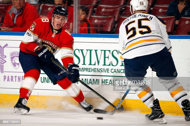 Reilly Smith of the Florida Panthers digs the puck out from the boards against Rasmus Ristolainen of the Buffalo Sabres at the BBT Center on April 8...
