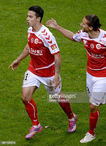 Reims' Brazilian midfielder Diego Rigonato Rodrigues celebrates with teammates after scoring a goal during the French L1 football match between Reims...