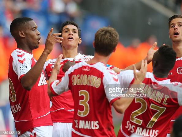 Reims' defender Jordan Siebatcheu is congratulated by his teammates on scoring during the French Ligue 1 football match between Reims and Paris...