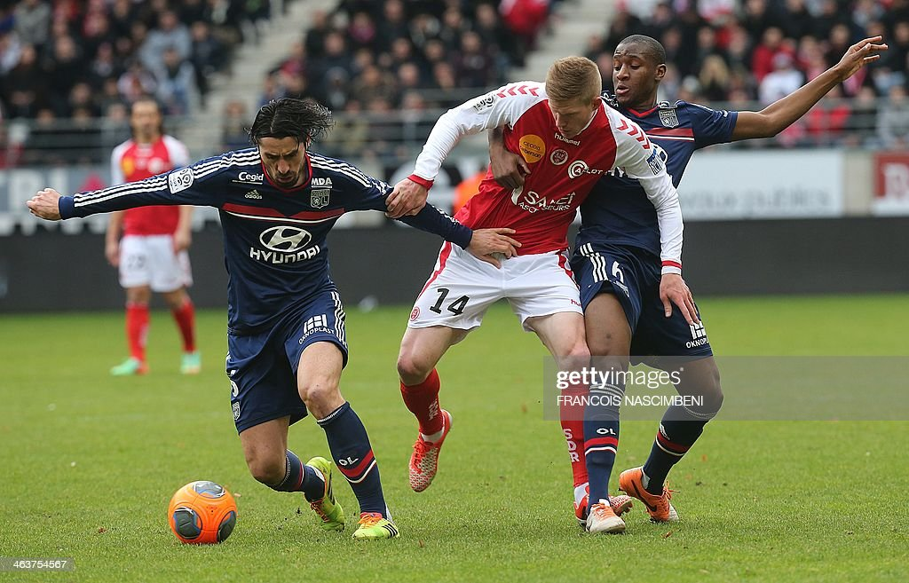 Reims' forward Gaetan Charbonnier (C) vies with Lyon's Serbian defender Milan Bisevac (L) and French midfielder Gueida Fofana (R) during a French L1 Football match between Reims and Lyon on January 19, 2014 at the Auguste Delaune Stadium in Reims.