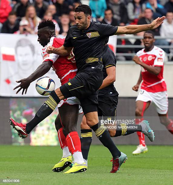 Reims' forward Grejohn Kyei vies with Seville's defender Adil Rami during a training football match between Reims and Seville on July 26 2015 at the...