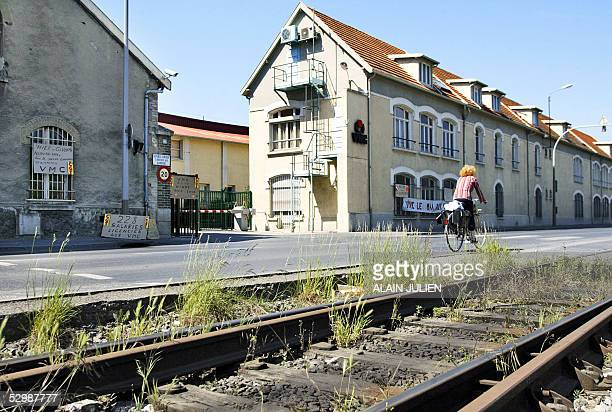 A cyclist rides past boards claiming for employement 27 May 2005 in Reims northeast of France at the entrance of the glass factory Verreries...