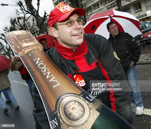 A man holds a cardboard champagne bottle during the demonstration of some 1000 people 17 January 2006 in Reims eastern France in support of the 450...