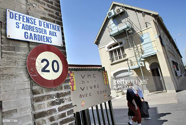 Workers walk past a board claiming for employement 27 May 2005 in Reims northeast of France at the entrance of the glass factory Verreries Mecaniques...