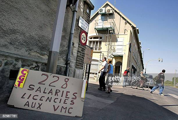 Workers walk past boards claiming for employement 27 May 2005 in Reims northeast of France at the entrance of the glass factory Verreries Mecaniques...