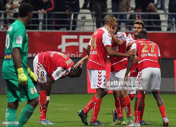 Reims' French forward David N'Gog celebrates with teammates after scoring a goal during the French Ligue 1 football match between Reims and Lille on...