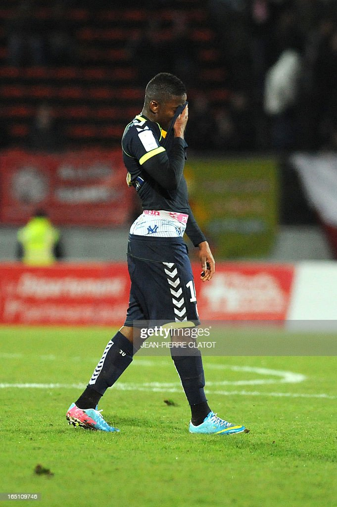 Reims' Togolese forward Floyd Ayite wipes his face with his jersey after receiving a red card during the French L1 football match Evian (ETGFC) vs Reims (SR) on March 30, 2013 at the city stadium Parc des sports in Annecy, eastern France.