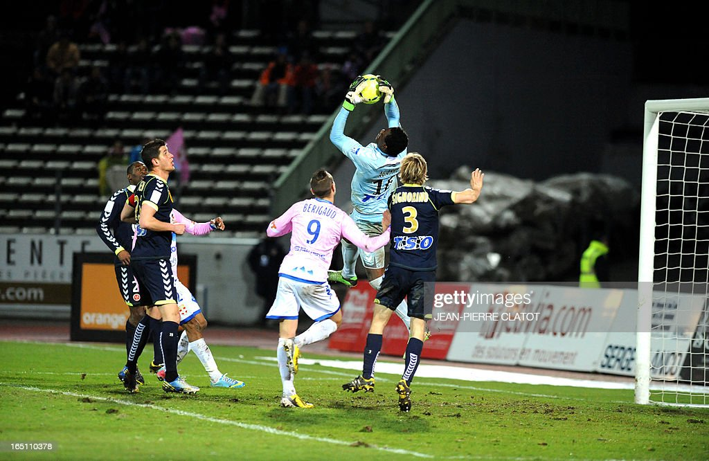 Reims' Togolese goalkeeper Kossi Agassa (C) jumps to grab the ball during the French L1 football match Evian (ETGFC) vs Reims (SR) on March 30, 2013 at the Parc des sports city stadium in Annecy, eastern France