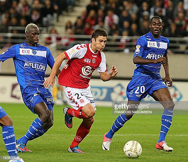 Reims'French midfielder Florent Ghisolfi vies with Troyes' forward Mohamed Yattara and Troyes' FrenchCongolese midfielder Granddi Ngoyi on September...