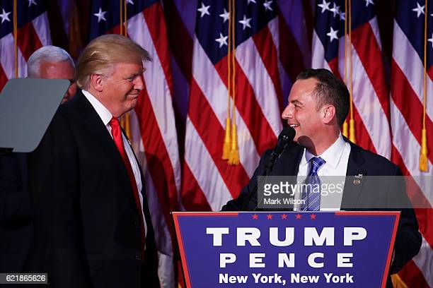 Reince Priebus chairman of the Republican National Committee delivers a speech as Republican presidentelect Donald Trump looks on during his election...