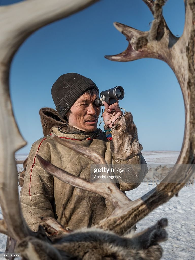A reindeer herder looks through binoculars at Nomad camp, 150 km from the town of Salekhard, Yamalo-Nenets Autonomous Okrug in Russia on May 2, 2016.