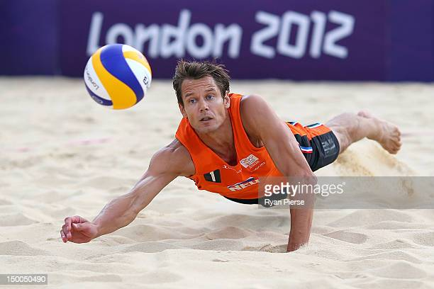 Reinder Nummerdor of Netherlands dives to attempt a return shot against Martins Plavins and Janis Smedins of Latvia during the Men's Beach Volleyball...