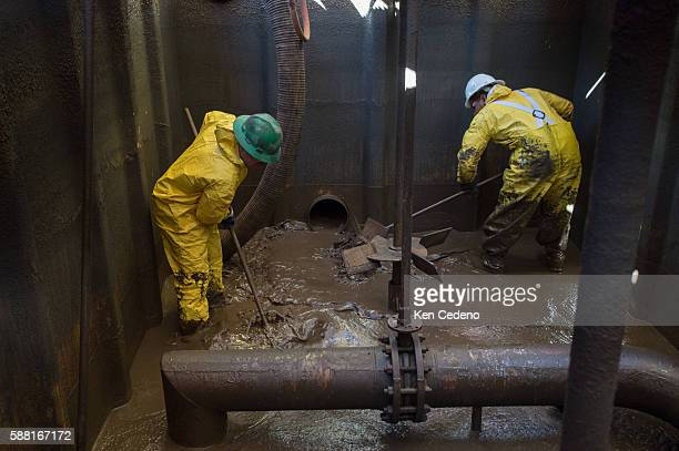 Reiner Perez left and Julio Perez right both floor hands work at vacuuming out remaining sediment in a storage tank on a Raven Oil Drilling rig near...