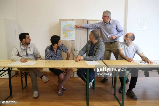 Reinhard Fischer who works for the city's Administration for Education Youth and Science points to a map of Germany as he leads men from Syria and...