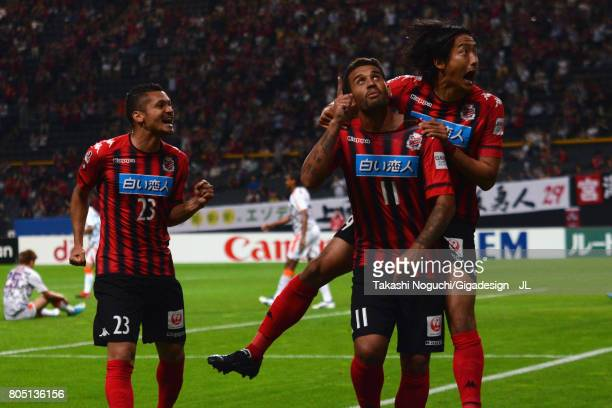 Reis of Consadole Sapporo celebrates scoring the opening goal with his team mates Macedo and Ken Tokura during the JLeague J1 match between Consadole...