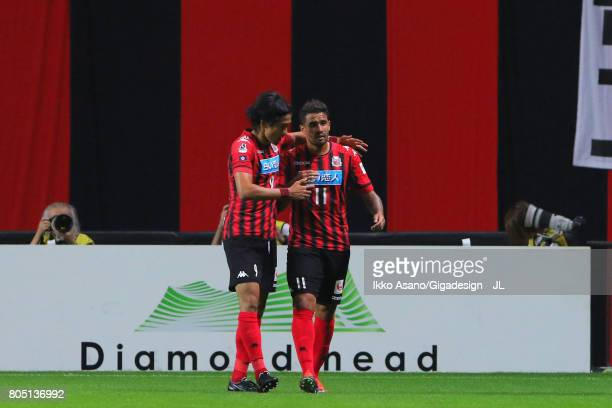 Reis of Consadole Sapporo celebrates scoring the opening goal with his team mate Ken Tokura during the JLeague J1 match between Consadole Sapporo and...