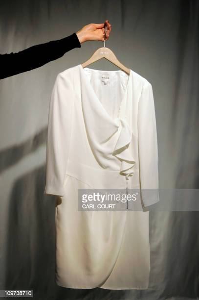 A Reiss employee holds a dress similar to the one worn by Kate Middleton in her official engagement photographs with Prince William at a store in...