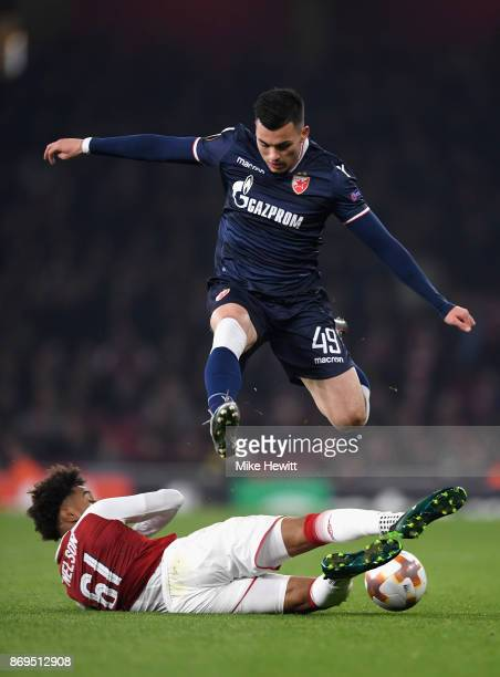 Reiss Nelson of Arsenal tackles Nemanja Radonjic of FK Crvena Zvezda during the UEFA Europa League group H match between Arsenal FC and Crvena Zvezda...