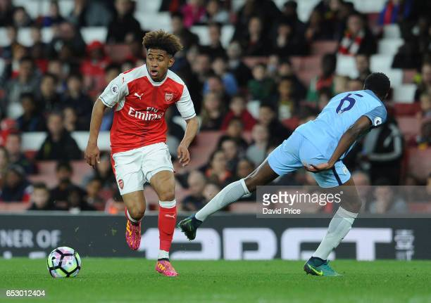 Reiss Nelson of Arsenal takes on Rodney Kongolo of Man City during match between Arsenal and Manchester City at Emirates Stadium on March 13 2017 in...