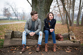 Young couple sitting on the bench in the park, having relationship difficulties.