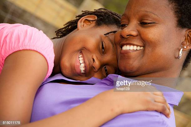 Relationships: African descent mother and daughter hug outside.